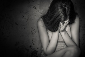 Black and white grunge image of a beautiful teenage girl sitting on the floor crying