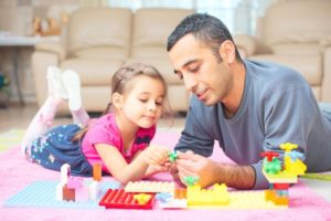 Father And Little Daughter Are Playing With Toys Together At Home